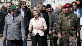 politician flanked by military people