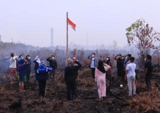 Sekelompok pemuda menggelar upacara bendera di area lahan gambut yang masih terbakar di Palangka Raya, Kalimantan Tengah, Sabtu (17/8/2019)