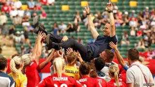 Head Coach Mark Sampson is hoisted in the air by the team.