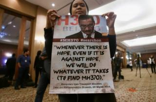 A family member of a passenger onboard the missing Malaysia Airlines flight MH370, shows a poster before the start of a news conference following a meeting with Joint Agency Coordination Centre (JACC) in Kuala Lumpur, Malaysia July 21, 2016.