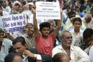 An Indian member of the Dalit caste community holds a placard saying 'In Gujarat, Cow Slaughter is a Sin while Killing Dalits is pardonable' (L) as he participates in a protest rally against an attack on Dalit caste members in the Gujarat town of Una, in Ahmedabad on July 31, 2016.