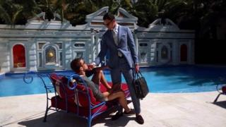 Two male models hold each other next to a swimming pool in an advert