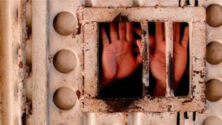 يد من وراء القضبان
