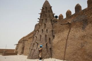 Ololgun aabo ajọ isọkan agbaye kan lati orilẹede Burkina Faso duro ni waju mọṣalaṣi Djinguereber to to ẹgbẹ̀ta (600) ọdun ni Timbuktu, Mali