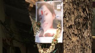 சம்பவம் நடைபெற்ற இடத்தின் அருகே மரத்தில் வைக்கப்பட்டுள்ள சந்தியாவின் படம்
