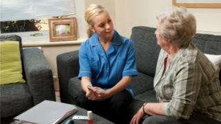 Medical staff member chats to patient