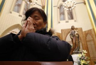 A woman prays at the Xishiku Catholic Church in Beijing, China