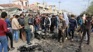 Des gens rassemblés autour des restes du véhicule détruit à la suite d'une explosion à Sadr City (le 2 janvier 2017)