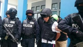Gerald Oropeza (second from right) is guarded by police before being handed over to Peruvian authorities in Huaquillas, Ecuador, on 13 September, 2015.