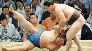 Two sumo wrestlers fight in the 2011 Nagoya Grand Sumo Tournament in Nagoya city in Aichi prefecture