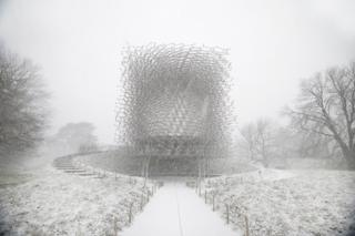 A snowy landscape with a honeycomb-style metal building
