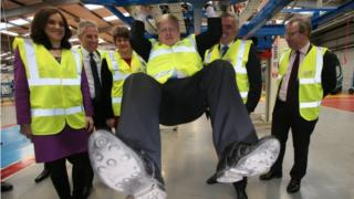 Boris Johnson swinging on the chassis of a Boris Bus at the Wrightbus plant in Ballymena