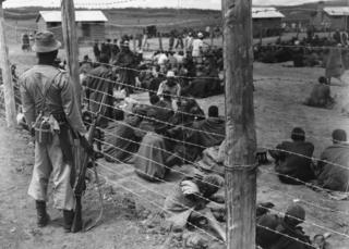 1952: Mau Mau suspects in a prison camp in Kenya. The Mau Mau Uprising (1952–1960), also known as the Mau Mau Rebellion, the Kenya Emergency, and the Mau Mau Revolt, was a war in the British Kenya Colony (1920–1963) between the Kenya Land and Freedom Army (KLFA), also known as Mau Mau, and the British colonists.