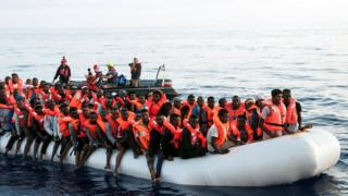 Migrants are seen in a rubber dinghy in the Mediterranean as they are rescued by the crew of Mission Lifeline, 21 June 2018.
