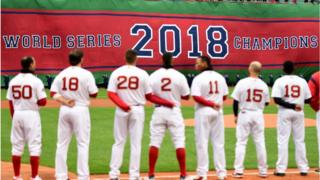 Red Sox team stands in front of banner reading: World Series 2018 Champions