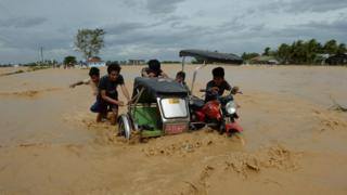 Residents push a tricycle on a flooded road in Santa Rosa town, Nueva Ecija province