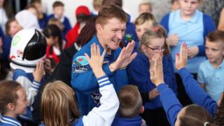 Major Tim Peake high-fives pupils from Blaenymaes Primary School