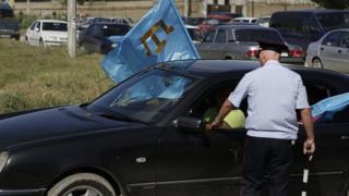 полицейский и машина с флагом крымских татар