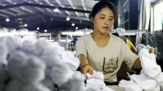 A woman works on socks that will be exported to the US at a factory in Huaibei in China's eastern Anhui province on August 7, 2018.