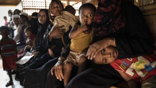 Children sit on laps in Cox's bazaar camp