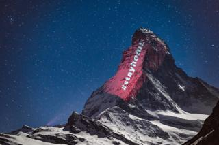 A light projection on to the side of a mountain with the message #stayhome