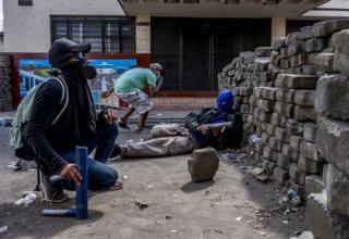 Masked youths with homemade mortars take cover behind a barricade as police bullets fly overhead