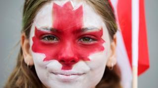 Una joven con la cara pintada con los colores de la bandera de Canadá.