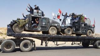 Iraqi federal police armoured vehicles are transported to the frontline outside Tal Afar (15 August 2017)
