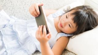 Menina deitada mexe no celular