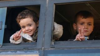 Syrian children, who were evacuated from rebel-held neighbourhoods in the embattled city of Aleppo, gesture as they arrive in the opposition-controlled Khan al-Assal region