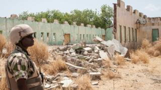 A soldiers stands next to a school destroyed by Boko Haram in Borno State, Nigeria