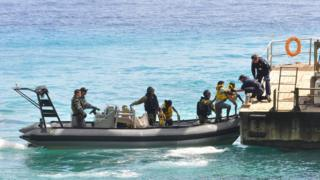 Australia navy delivers asylum seekers, intercepted on a boat, to Christmas Island (file image from 2013)