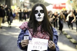 "A woman holds a sign that reads ""machismo kills"" during a demonstration in Santiago, Chile, 06 June 2018."