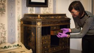 Curator Ruth Martin with a 260-year-old Chippendale secretaire