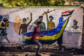 A Sudanese protester runs past mural depicting scenes from recent demonstrations.