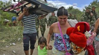 A Colombian woman cries as she arrives with her daughter in Cucuta after crossing the border on 26 August, 2015