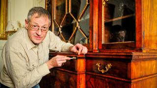 Conservation expert James Hardie working on the bookcase