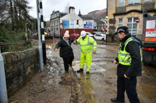 A local resident, escorted through the debris left by receding floodwater in Mountain Ash, Wales