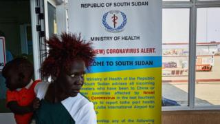 A passenger walks past a coronavirus health sign in South Sudan