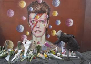 Flowers left below a mural of David Bowie on the wall of a Morley's store in Brixton, London