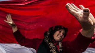 An Egyptian woman dances before a large national flag in Cairo's northern suburb of Shubra al-Khaymah on the second day of voting in the 2018 presidential elections on 27 March.