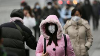 12月21日,北京街头,一处办公区域附近戴口罩的行人。