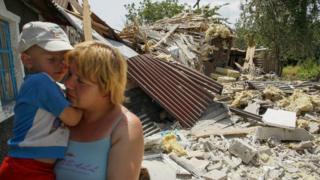 Женщина на развалинах дома