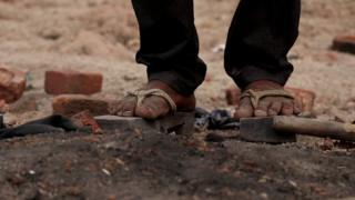 लकड़ी की चप्पलें पहनकर काम करते मजदूर