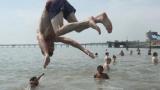 People enjoy the hot weather at Southend beach in Essex.