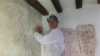 Peter Martindale working to restore the paintings