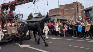 Xolo the Dog walks past crowds