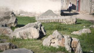 Fragments of concrete blocks remain on the razed compound