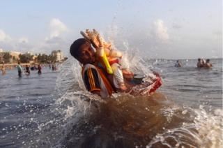A devotee carries an idol of the Hindu god Ganesh, the deity of prosperity, into the Arabian Sea on the second day of Ganesh Chaturthi festival in Mumbai