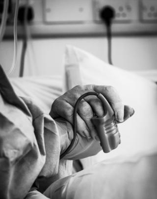 Intensive care unit staff holding a patents hand